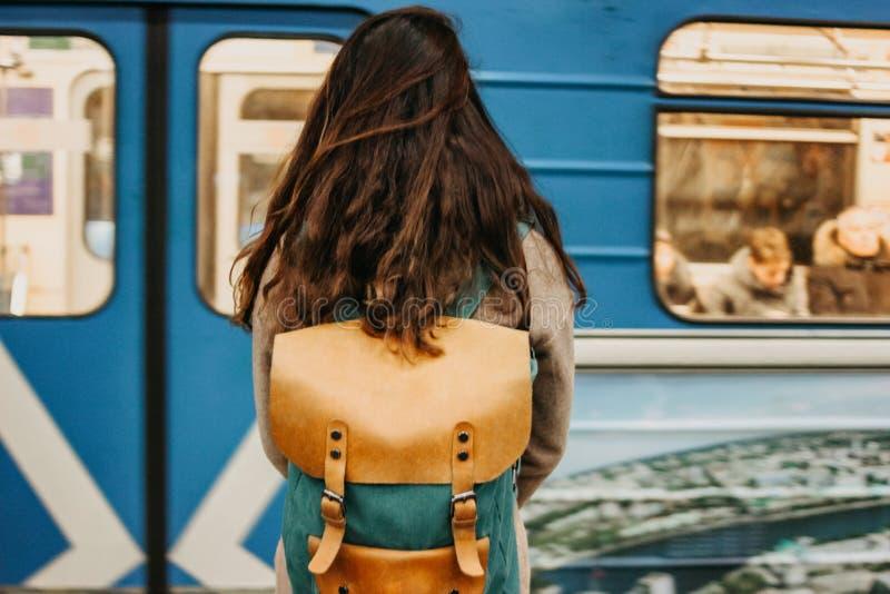 有背包的年轻女人卷曲红色顶头女孩旅行家和地图在火车前面的地铁 图库摄影