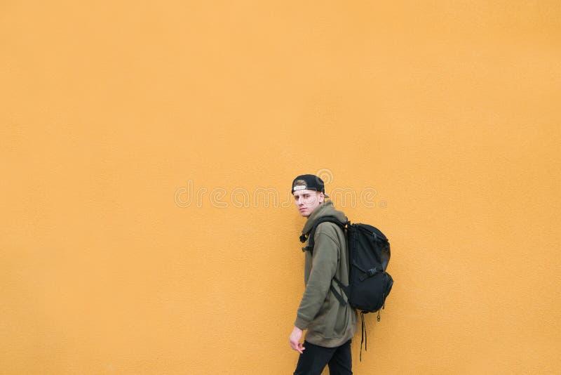 有背包的时髦的街道年轻人在大橙色墙壁的背景站立 Copyspace 免版税库存图片