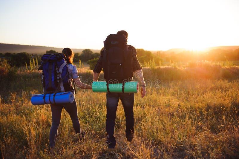 有背包的走在日落的两个远足者剪影 迁徙和享受日落视图 免版税库存照片