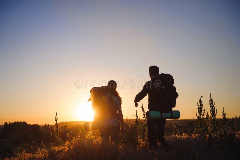 有背包的走在日落的两个远足者剪影 迁徙和享受日落视图 库存图片
