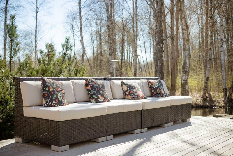 有藤条庭院家具集合的大大阳台露台 与坐垫的木庭院躺椅 舒适的藤条沙发 放松 免版税库存照片