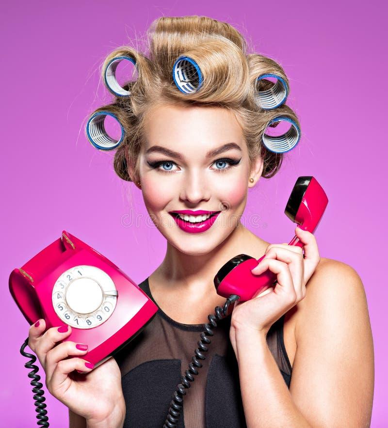 有蓝色卷发的人的微笑的女孩谈话由一个老红色电话 免版税库存照片