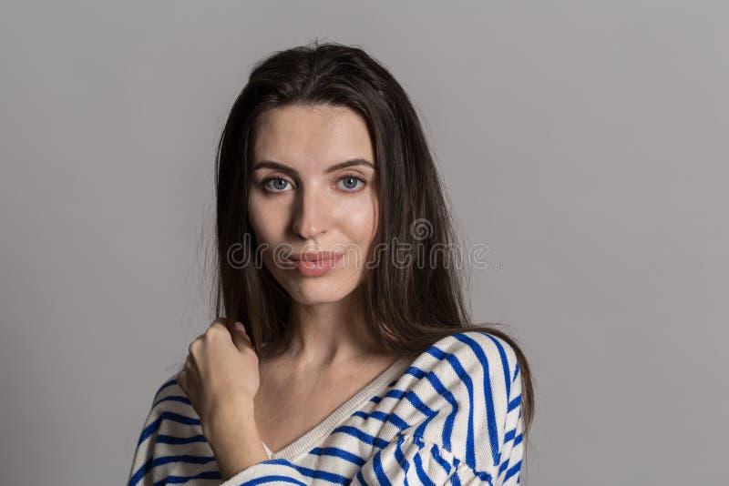 有蓬松头发的俏丽的妇女,穿戴随便对灰色演播室墙壁 免版税库存图片