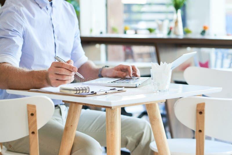 有膝上型计算机和纸的庄稼人在咖啡馆 库存图片