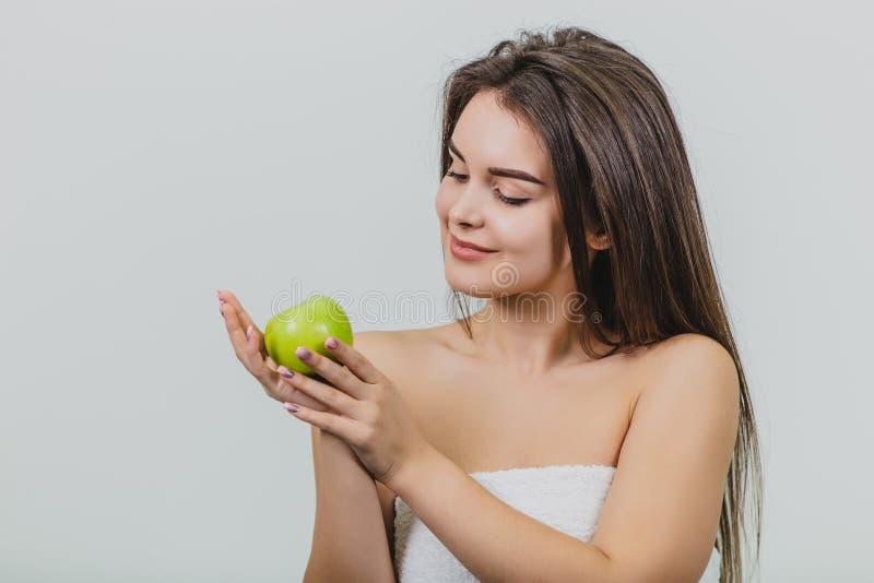 有自然自然构成的美丽的少女和完善的皮肤用苹果在她的手上 秀丽拍的面孔照片 免版税库存照片