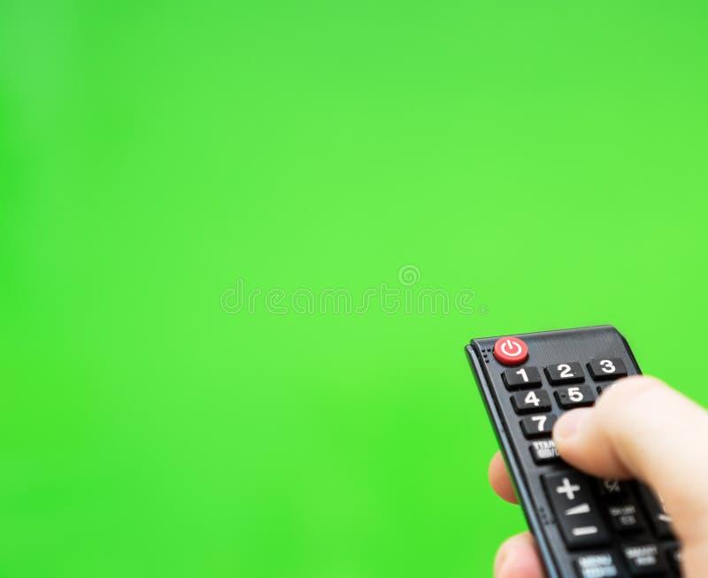 有遥控的电视的男性手 库存照片