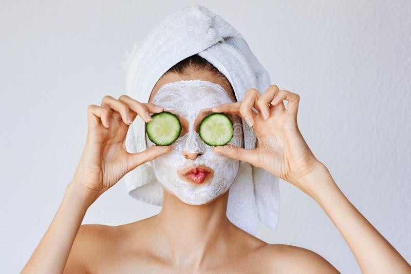 有面膜的美丽的年轻女人在她的拿着切片黄瓜的面孔 皮肤护理和治疗,温泉,自然美人和 库存图片