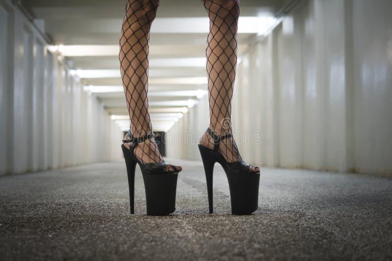 有非常高跟鞋的黑鞋子 有美好的苗条腿的一名妇女是在地下过道的隧道 免版税库存图片