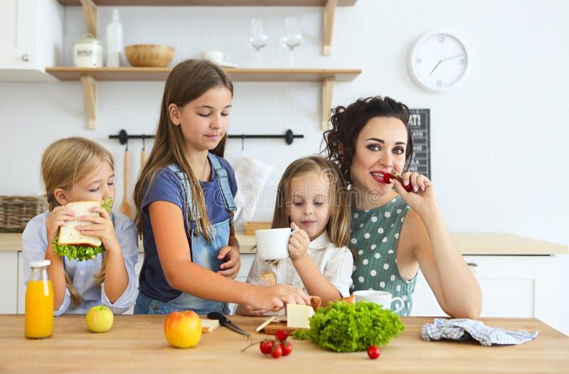 有食用逗人喜爱的小孩的愉快的年轻深色的母亲早餐 免版税图库摄影