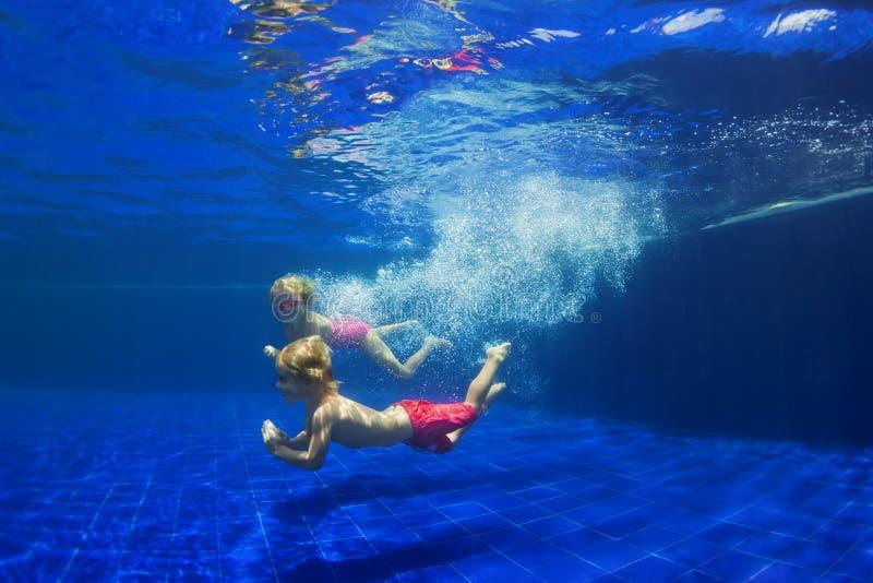 有鳍的孩子在游泳场潜水水下 库存照片
