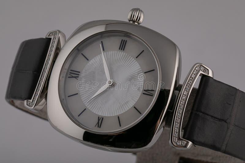 有黑皮带的妇女的手表,与金刚石,在银色身体,灰色拨号盘,罗马数字隔绝在灰色背景 库存照片