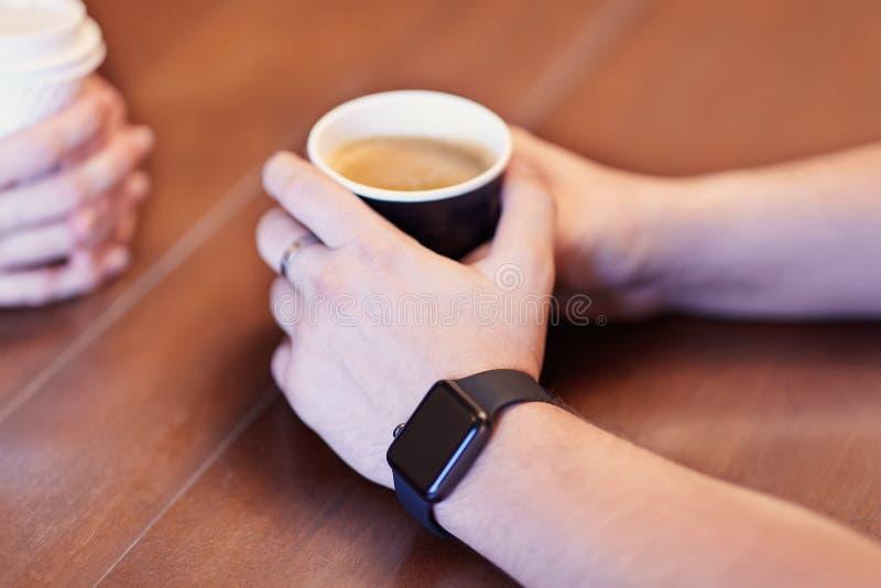 有黑电子手表的人手,拿着黑咖啡 在背景的其他手与白色杯子,木桌 Da 图库摄影