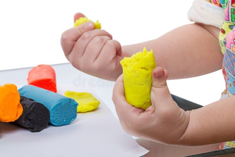 有黄色彩色塑泥的孩子 库存照片