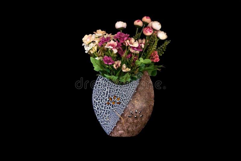 有黄色,红色的美丽的花瓶,桃红色、紫色塑料花和叶子在坚实黑背景中 库存照片