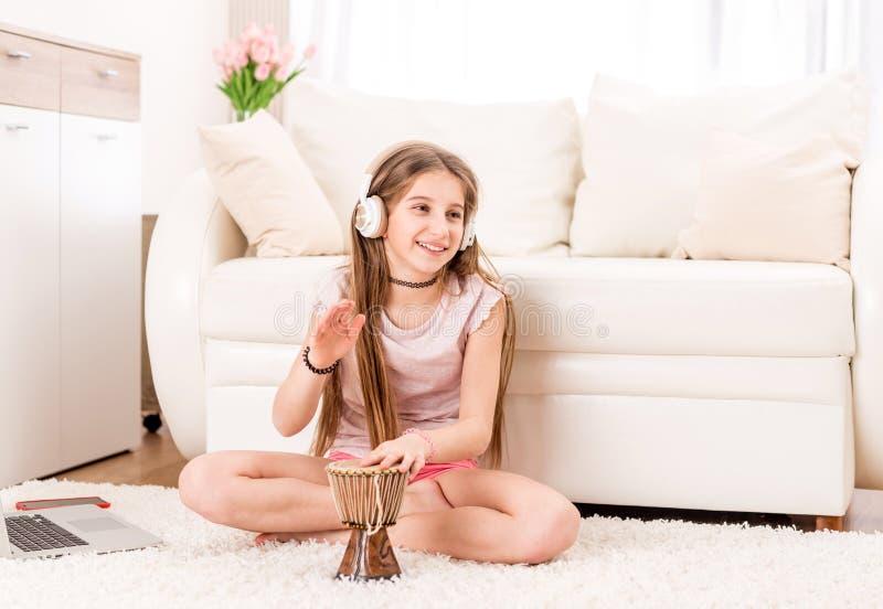 有鼓和耳机的微笑的女孩少年 库存图片