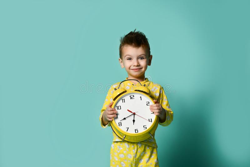 有闹钟的逗人喜爱的小男孩,在蓝色 指向闹钟的滑稽的孩子早晨 免版税库存照片