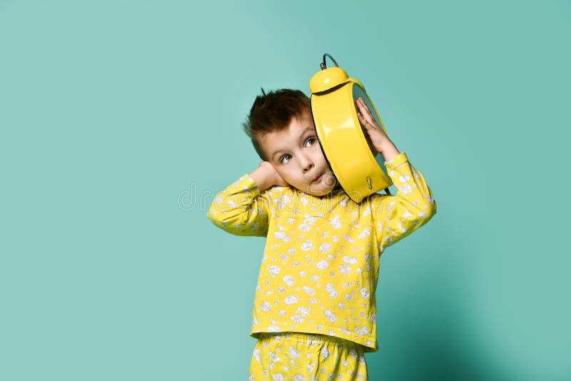有闹钟的逗人喜爱的小男孩,在蓝色 指向闹钟的滑稽的孩子早晨 免版税库存图片