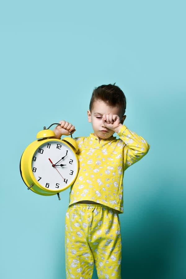 有闹钟的逗人喜爱的小男孩,隔绝在蓝色 指向闹钟的滑稽的孩子早晨 图库摄影
