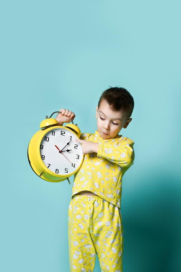 有闹钟的逗人喜爱的小男孩,隔绝在蓝色 指向闹钟的滑稽的孩子早晨 免版税库存照片