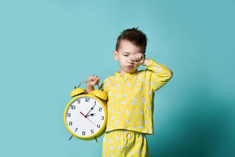 有闹钟的逗人喜爱的小男孩,隔绝在蓝色 指向闹钟的滑稽的孩子早晨 免版税库存图片