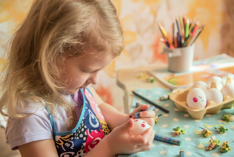 有铅笔的女孩绘在复活节彩蛋的滑稽的面孔 家庭准备的假日复活节 图库摄影