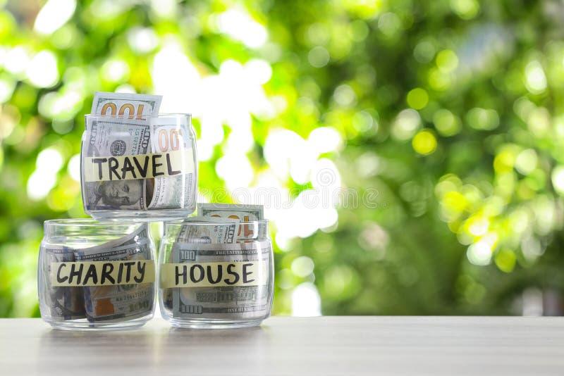 有金钱的玻璃瓶子在桌上的不同的需要的 免版税库存图片