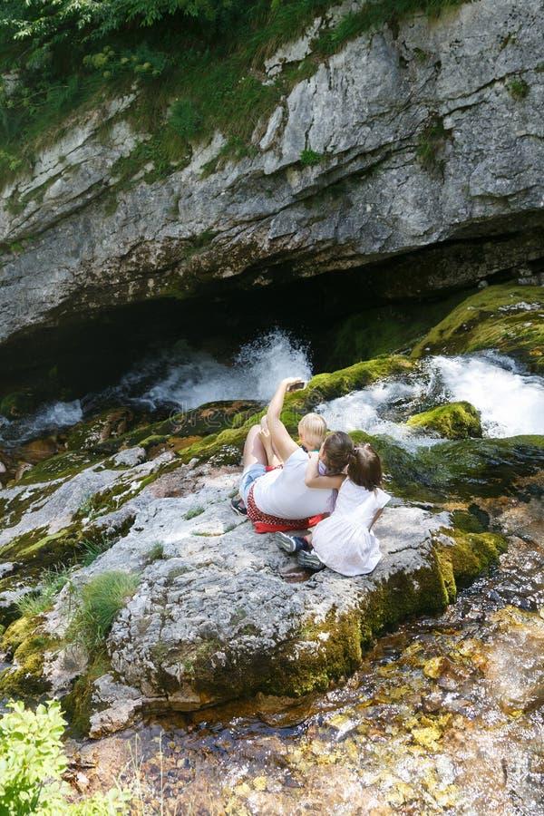 有采取selfie的孩子的母亲,坐岩石由在家庭旅行的一条山小河 库存图片