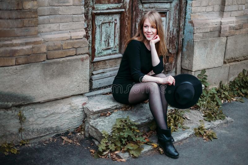 有长发的白肤金发的微笑的女孩,在有一个帽子的黑礼服在他的手上,坐在葡萄酒背景的步  库存图片