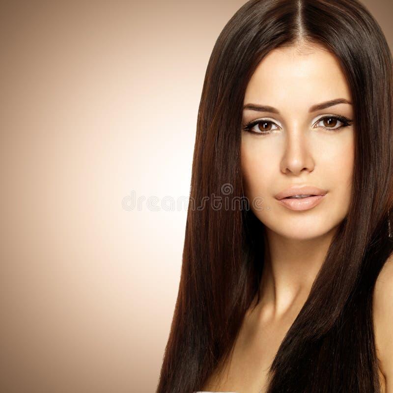 有长期平直的棕色头发的美丽的妇女 免版税图库摄影
