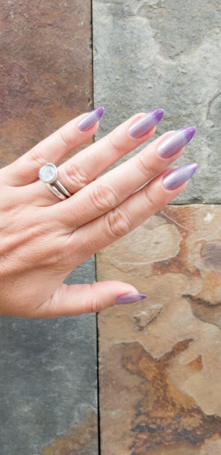 有长的拿着瓶的钉子和桃红色修指甲的女性手 免版税库存图片