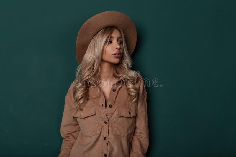 有长的美丽的卷发的年轻女人在一件米黄时兴的衬衣的一个典雅的米黄帽子有自然构成的 图库摄影