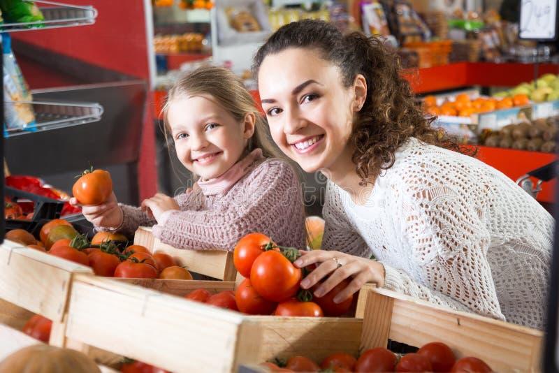 有选择蕃茄的美丽的女儿的年轻女人在商店 库存图片
