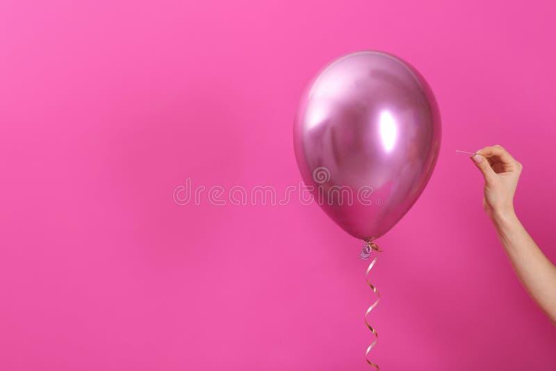 有针的妇女刺穿的气球在颜色背景,特写镜头 图库摄影