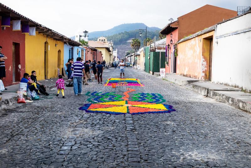 有alfombre花地毯的五颜六色的房子在安提瓜,危地马拉的被修补的街道上 库存照片