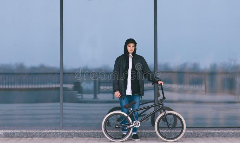 有BMX自行车的年轻人在黑暗的墙壁的背景站立 BMX车手画象  街道文化 图库摄影
