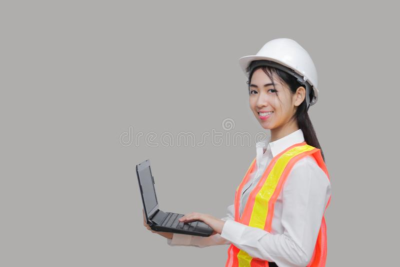 有safty设备运载的膝上型计算机的秀丽确信的年轻亚裔工作者在灰色被隔绝的背景 库存照片
