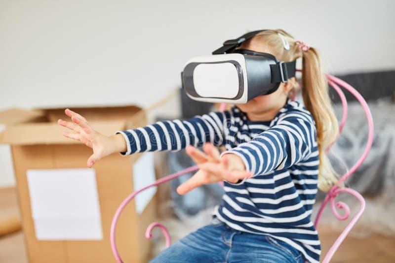有VR玻璃戏剧的女孩在新房里 免版税图库摄影