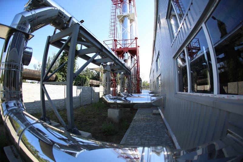 最新的代用燃料锅炉室的广角全景照片有管子的,塔和坦克,在一个清楚的夏日 库存照片