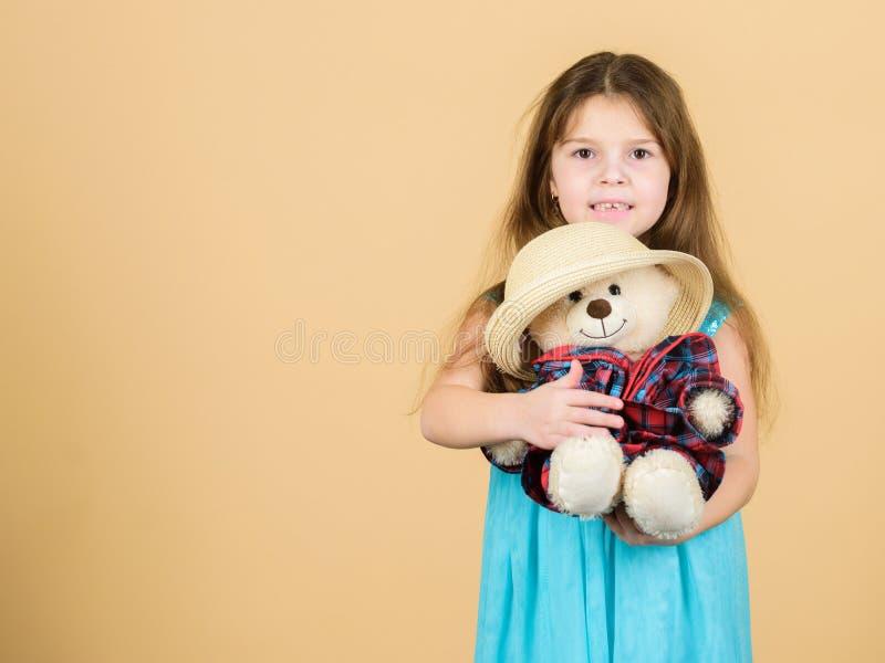 最逗人喜爱  仔细孩子女孩拥抱软的玩具玩具熊米黄背景 嫩附件 小女孩举行 免版税库存图片