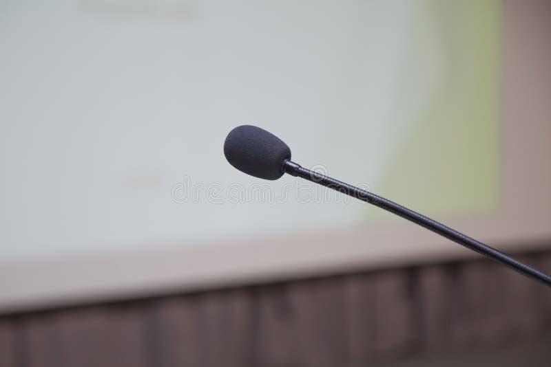 报告人在谈话准备与在指挥台后的观众前集中话筒于指挥台和被弄脏的空位进去和一些 免版税库存照片