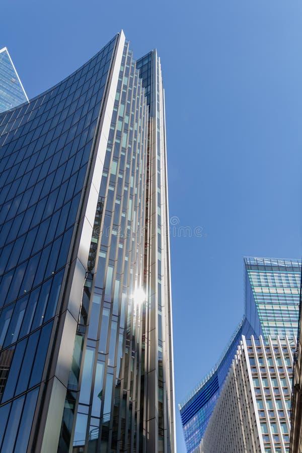 抽象玻璃门面在天空蔚蓝背景的一明亮的好日子 经济财务和商务活动概念 免版税库存图片