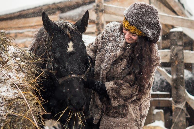 抚摸在雪的特写镜头女孩幼小逗人喜爱的驹 库存照片