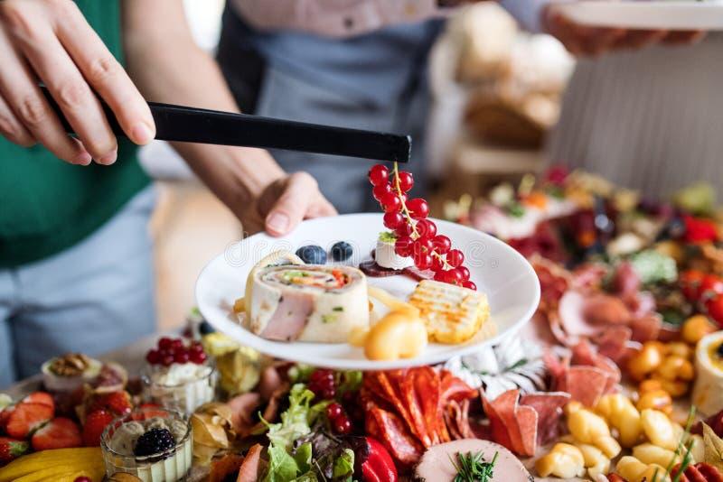 把食物放的妇女的中央部位在一室内家庭生日宴会的板材上 免版税图库摄影