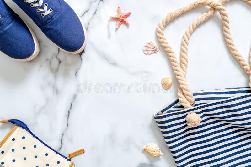 暑假构成 时兴的蓝色运动鞋,镶边海滩袋子,贝壳,在大理石背景的海星 妇女` s书桌 图库摄影