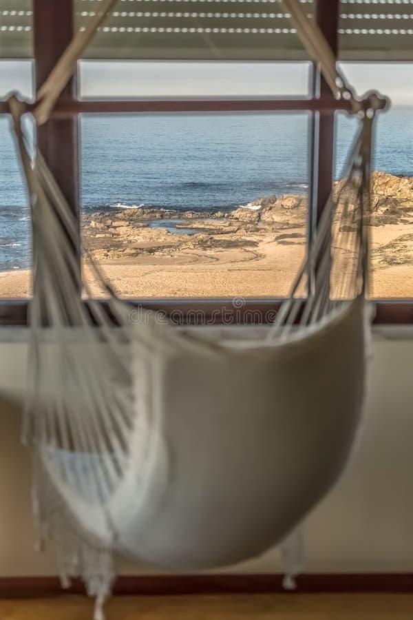 暂停的椅子看法在俯视多岩石的海滩的房子客厅 库存图片