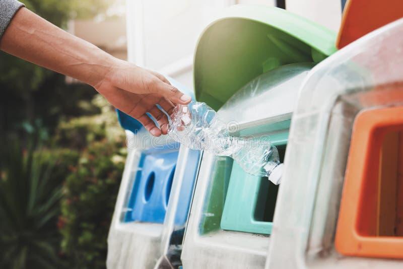 投入塑料瓶的人们回收站 库存照片