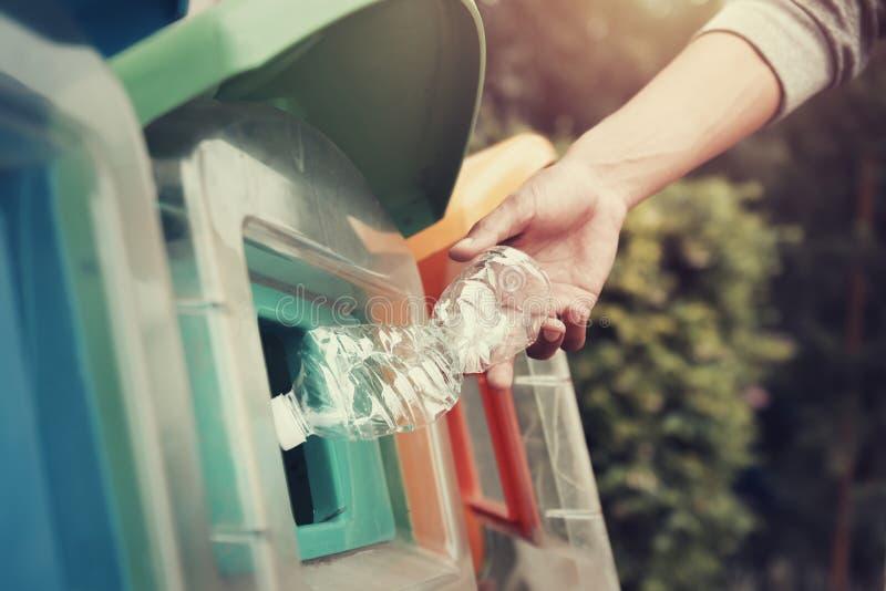 投入塑料瓶的人们回收站 库存图片