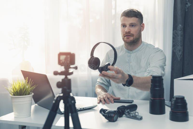 技术博客作者录音在照相机前面的耳机回顾在家 免版税库存照片
