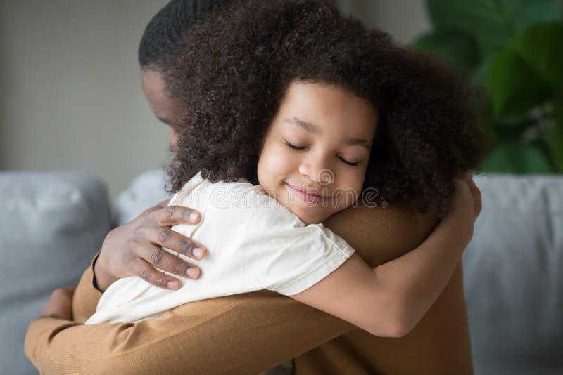 接受父亲感觉的爱连接的逗人喜爱的混合的族种儿童女儿 免版税库存照片