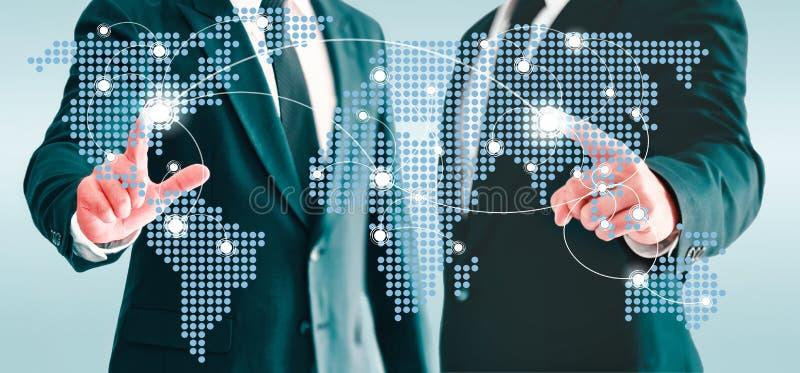 接触世界地图真正按钮的两个商人 信息和商务联系被互联的世界的概念 库存照片